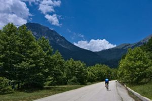 Road cyclist is cycling on empty roads in Greece with verdant scenery and mountain tops