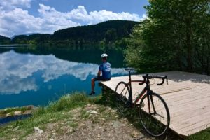 Roa cyclists is resting with his rental bike close to the Doxa Lake beachfront