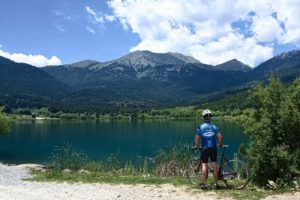 A road Cyclist overlooks Feneos lake, which is part of the Epic cycling trip