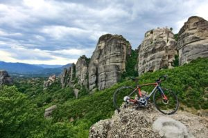 View of a road bike in front of the imposing rock formation of Meteora