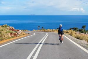 Woman cyclist is cycling along an empty coastal road with perfect tarmac