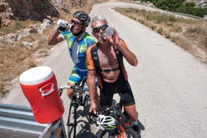Cyclists drinking water while cycling uphill in Leonidio