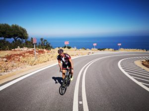 Cyclist is cycling on a bautiful coastal road in Leonidio