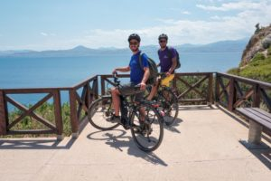 Cyclists ebiker at Vouliagmeni Lagoon Greece