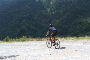 Cyclists is riding on a gravel bike traversing rich Olympus forests
