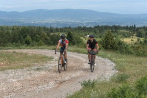 Two cyclists on grvels bikes with the view of Olympus Valley