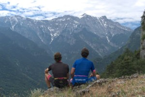 Cyclists resting in front of the mt. Olympus summit with view at the glaciers