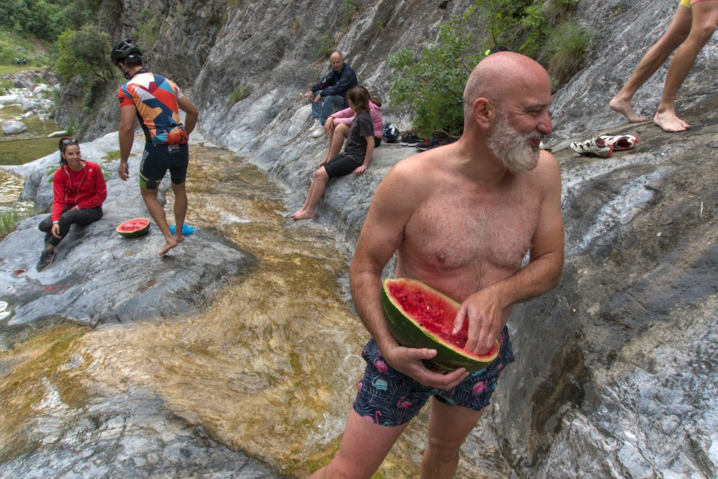 Cyclists enjoy a fresh watermelon during their break