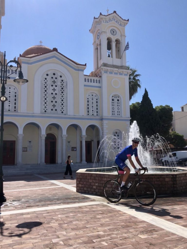 A cyclist posing in front of an iconic church in Keratea