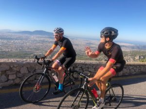 Two cyclists on road bikes are climbing up mt Parnitha and looking at the skyline of Athens