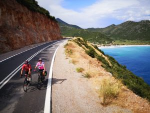 A road cyclist and an ebiker lady are cycling on a beautiful coastal road in eastern Peloponnese