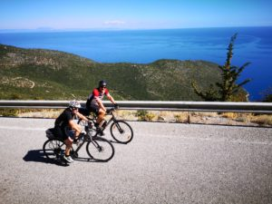 Mature cycling couple enjoys cycling of greek coastal roads in the Peloponnese