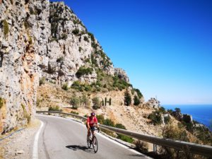 Mature road cyclist is cycling along a winding rugged coastal road in the Peloponnese