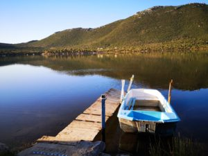 A boat on a calm lake part of Peloponnese cycling break