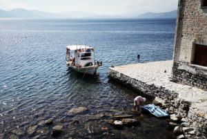 A fishing boat and a lady painting the stones with the Greek flag as captured by cyclists in Pelion