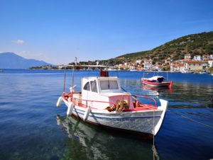 A fishing boat in the blue water of Pelion, as captured by cyclists