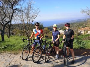 Cyclists posing for a photograph with the Pelion views of the sea in the background