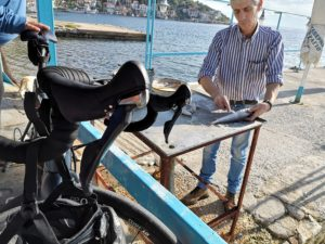 A bike in front of fisherman who is cleaning fishes in Pelion