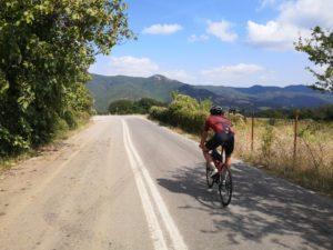 Cyclist is cycling through a mountain range in Olympus region