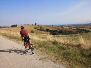 Cyclist is biking throught the farmfields around the mountain Olympus