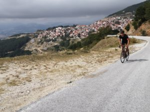 Cyclist is climbing from a mountain village neat the Olympus region