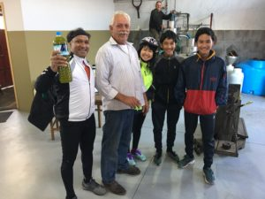 A family of cyclists has stopped to witness how a olive oil is produced