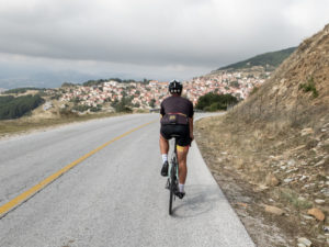A cyclist descends towards a village at the banks of Mountain Olympus