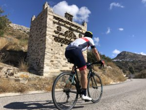 A cyclist is passing a traditional dove cote in Tinos Island.