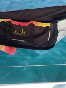 Our cycling kit is drying on the catamarans rails, with fluorescent water in the background