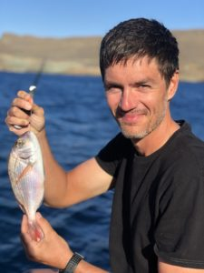Our cycling guide is holding fresh fish, ready for the dinner on the sailing boat