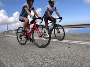 Cycling couple enjoy a panoramic view of the island's top