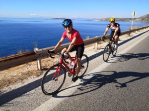 Cyclists riding along the coastal roads of the Greek Islands during their sailing trip