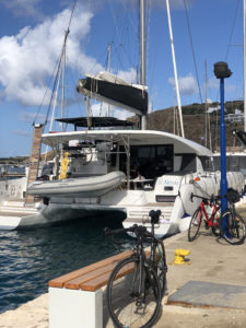 Bikes and a catamaran ssailing boat at a port, just before the cycling begins