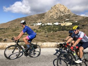 Cyclists are riding their roads bike on Tinos, with the mt. Xomvourgo in the background