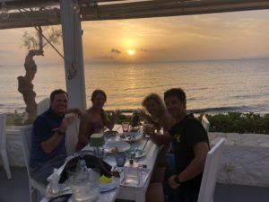 Cyclists enjoy a dinner meal by the sunset while sailing at the islands