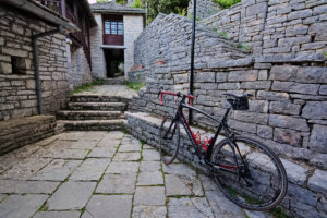 A road bike in front of Epirus style white stone building