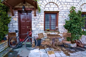 A road bike in front of a traditional, stone built guesthouse in Epirus