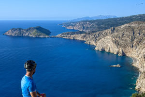 Cyclist overlooking the sea and the rugged terrain in Kefalonia Island