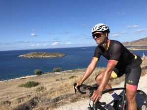 Cyclist is riding his road bike on a Greek island, whist he is happy
