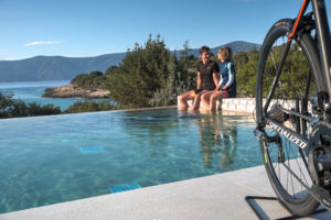 A cycling couple is chating at the infinitiy pool, right after their road cycling session