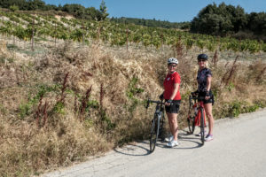 Two female cyclists in front of a wine hill in Nemea during a wine tour