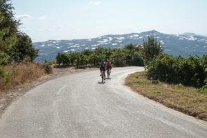 Two female cyclists on a winding vine road in Nemea Greece
