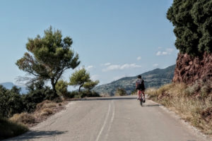 Cyclist on a road bike in Nemea, going downhill on a winding road