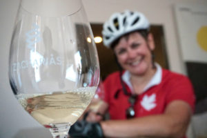 Female cyclist during the wine tasting is having a nice time