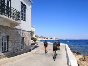 Road cyclists are biking through the town of Spetses