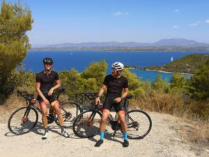 Cyclists on road bikes are posing, with the sea and island of Spetses in the background