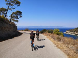 Cyclists on roac racing bikes cycling on a spectacular coastal road on Spetses