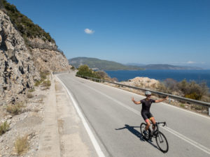 Cyclist on a road bike on a superb coastal road in the Peloponnese
