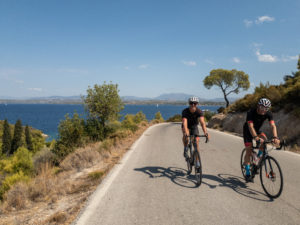 Two cyclists on road bikes on Spetses coastal road