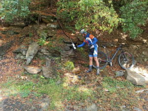 Mountain biker is filling his bottle from a water spring